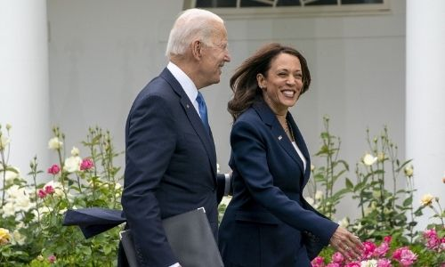 President Joe Biden and Vice President Kamala Harris smile as they walk off after an event updating.